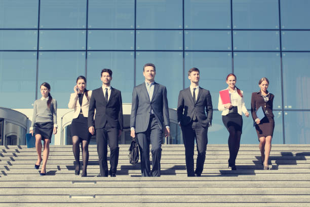 Business people walking down stairs stock photo