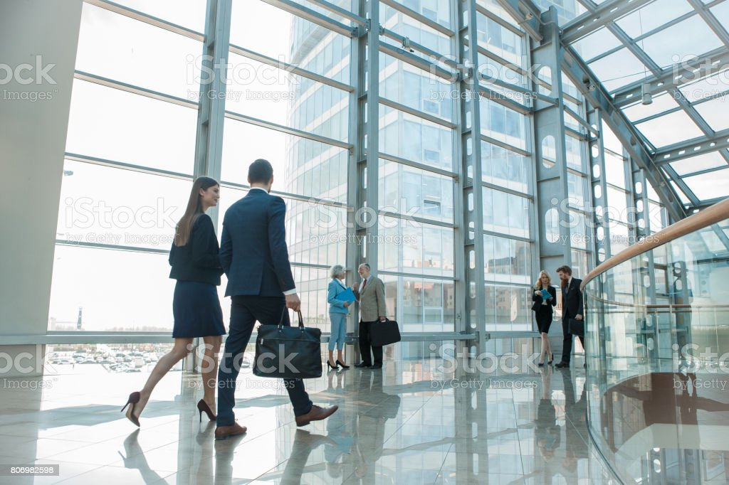 Business people walking in glass building - foto stock