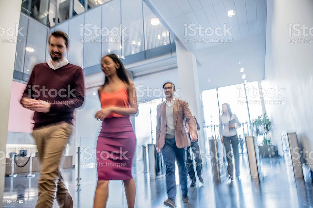 Business people walking in modern office, blurred motion stock photo