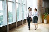 Two young female and male business people talking and walking along window in office. Woman is gesturing and smiling.