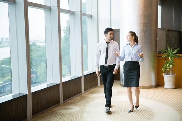 business people walking in office 1 - knotenkleid stock-fotos und bilder