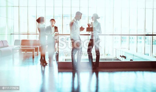 istock Business people walking in the office building lobby 611172524