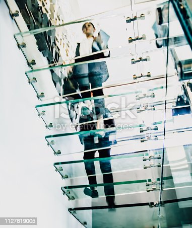 180698194 istock photo Business people walking on modern glass staircases 1127819005
