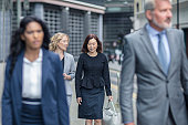 Business people walking on sidewalk in city