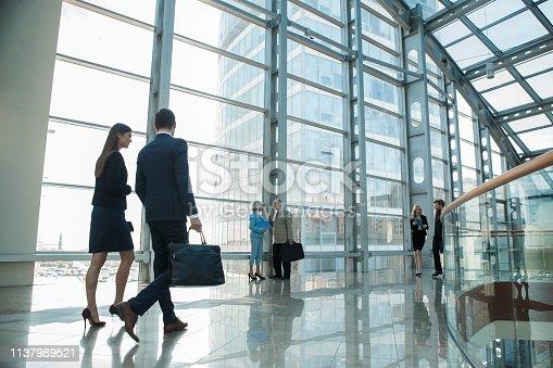 Business people walking on a modern walkway in office building