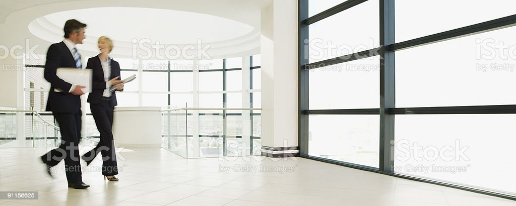 Business people walking through office lobby royalty-free stock photo