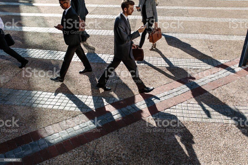 にぎやかな通りの朝オフィスに歩くビジネスマン - オフィスのロイヤリティフリーストックフォト