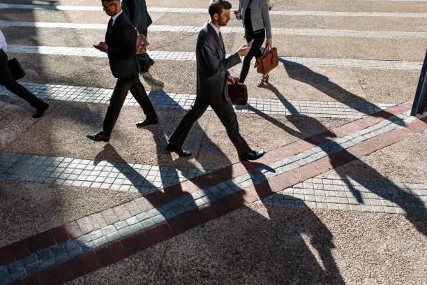 mensen uit het bedrijfsleven lopen naar kantoor in de ochtend op een drukke straat - forens stockfoto's en -beelden