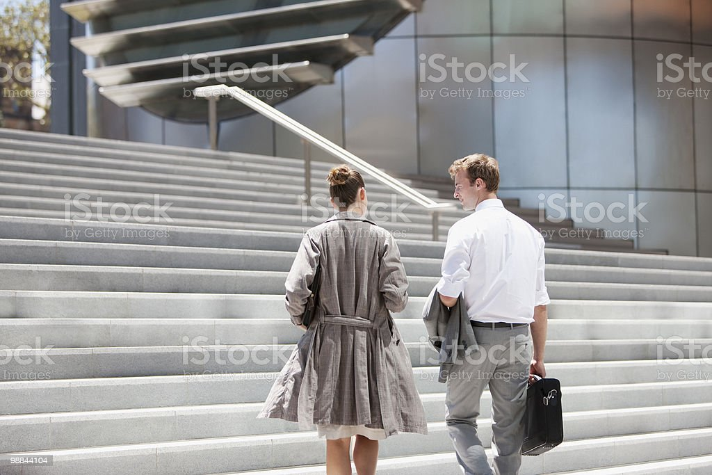 Business people walking toward steps outdoors royalty free stockfoto