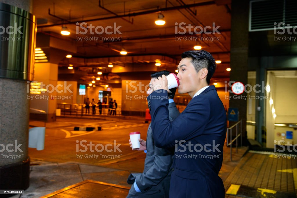 Business people walking with coffee, discussing royalty-free stock photo