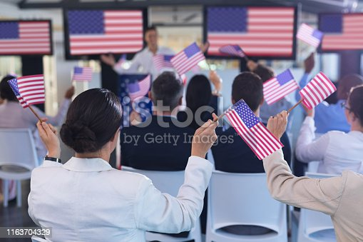 1133973551 istock photo Business people waving an American flag in business seminar 1163704329