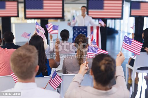 1133973551 istock photo Business people waving an American flag in business seminar 1163704334