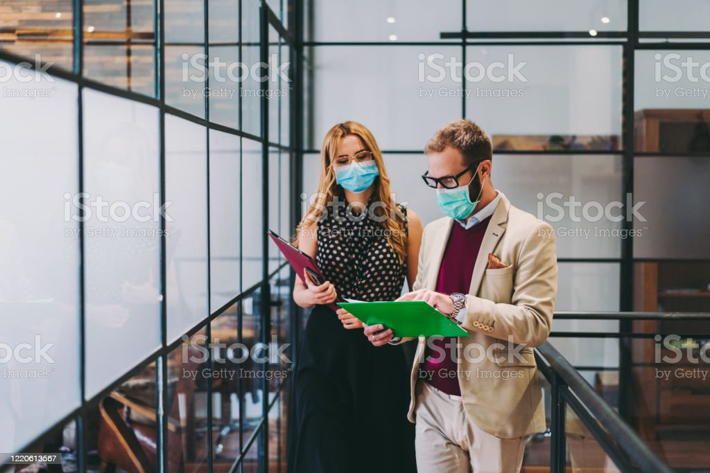 Business people wearing face masks at work during COVID-19 pandemic - Foto stock royalty-free di Adulto