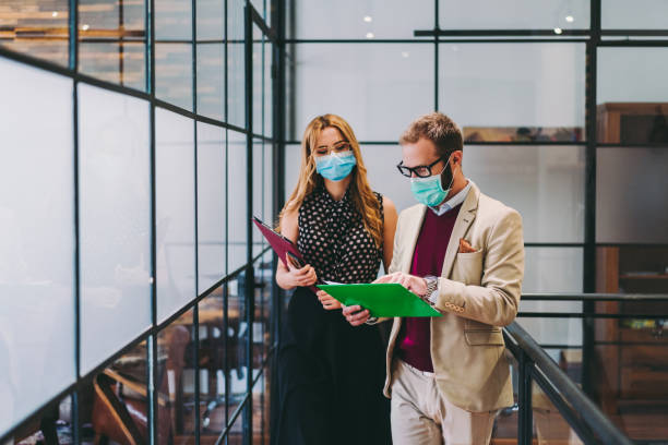 Business people wearing face masks at work during COVID-19 pandemic stock photo
