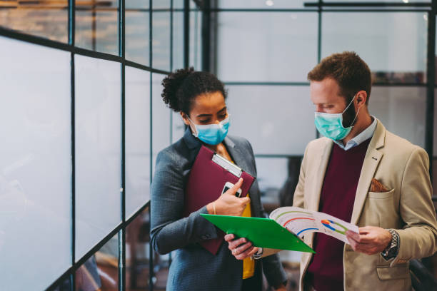 Business people wearing protective face masks at work during COVID-19 pandemic stock photo