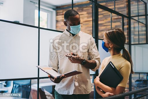 Businesspeople wearing masks in the office for illness prevention during COVID-19 pandemic