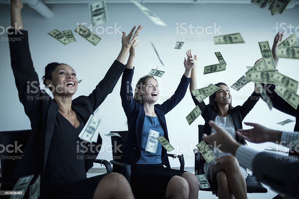 Business people with arms raised throwing money in the air stock photo