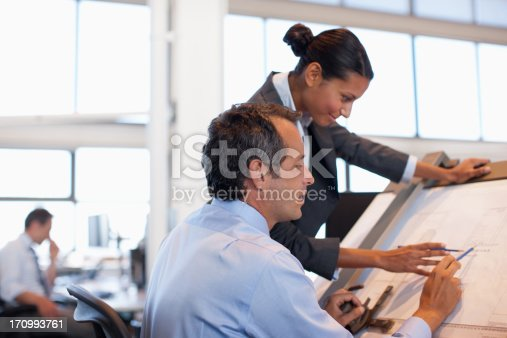 istock Business people with blueprints and model building 170993761