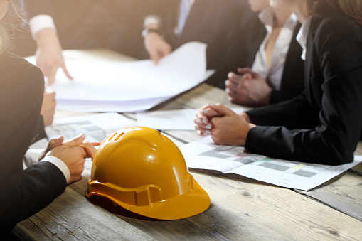 Business people discuss construction blueprint, hardhat on office table