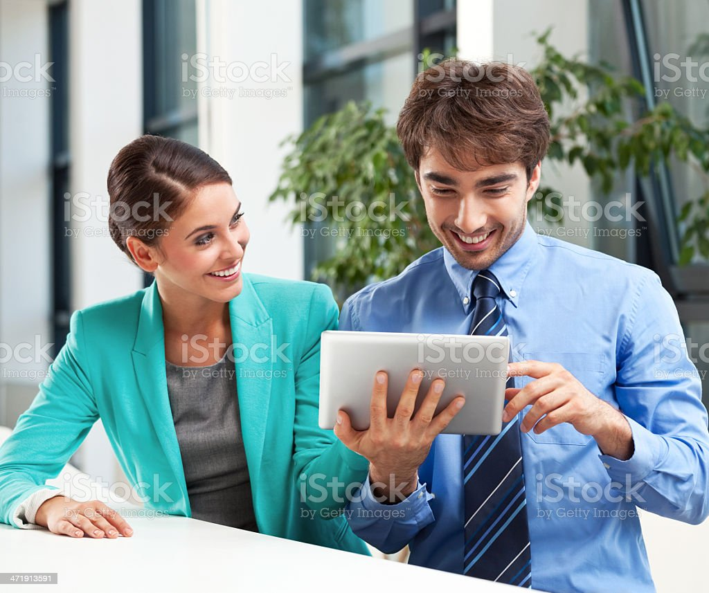 Business people with digital tablet Cheerful business couple using a digital tablet together. Adult Stock Photo