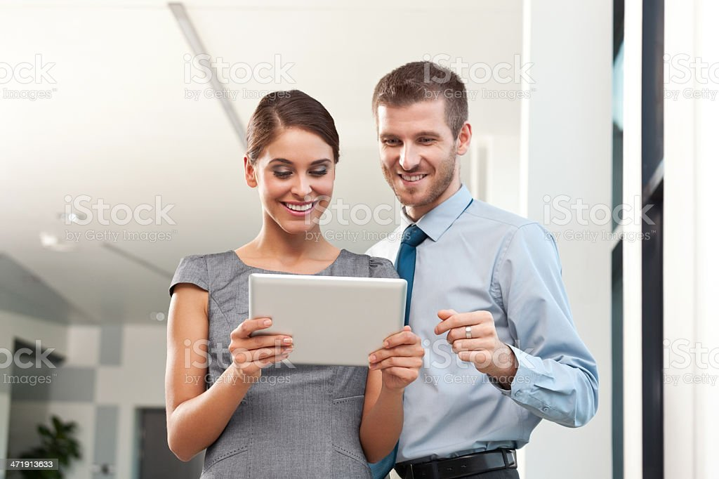 Business people with digital tablet Businesswoman and businessman watching at digital tablet.  Adult Stock Photo