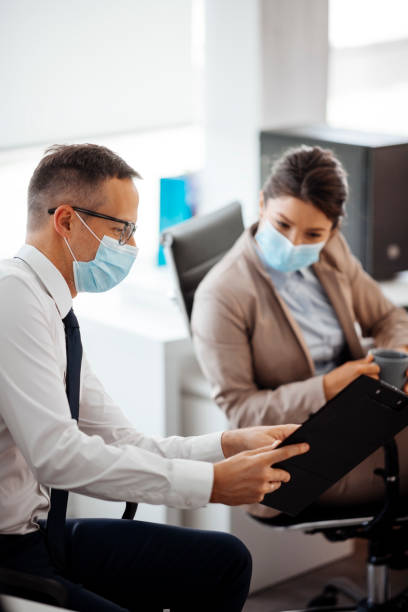 Business people with facemask discussing during coffee break at office stock photo stock photo