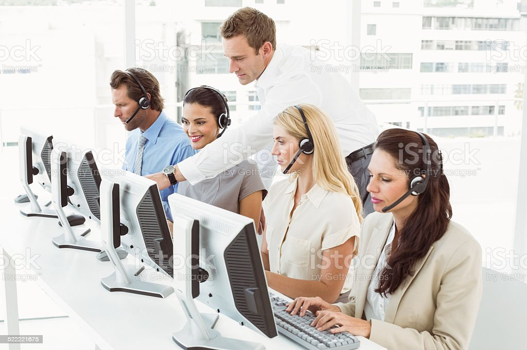 Business people with headsets using computers in office stock photo