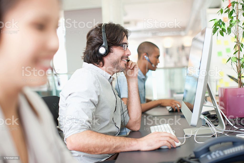 Business people with headsets working at computers in office royalty-free stock photo