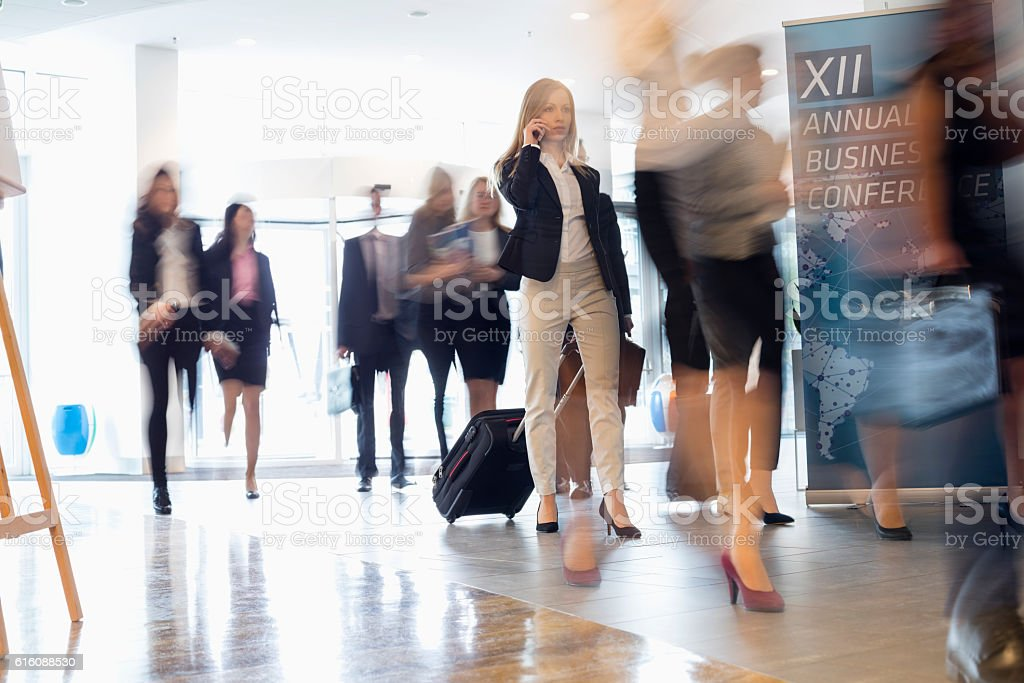 Business people with luggage walking at convention center stock photo