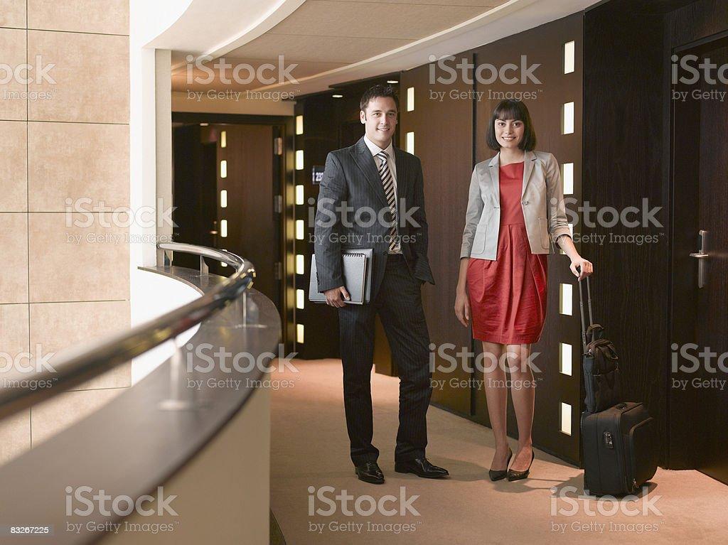 Uomini d'affari con i bagagli in piedi nel corridoio dell'hotel foto stock royalty-free
