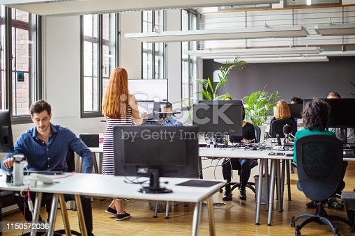 Business colleagues working at a busy open plan office. Startup business people group working everyday job at modern office.