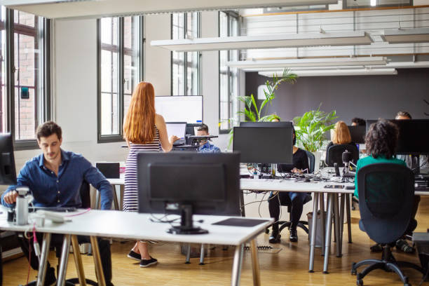 Business people working at a busy open plan office stock photo