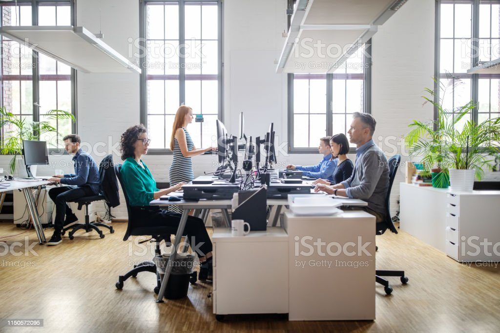 Business people working at a modern office Business people at their desks in a busy, open plan office. Startup business people working at a modern office. Office Stock Photo