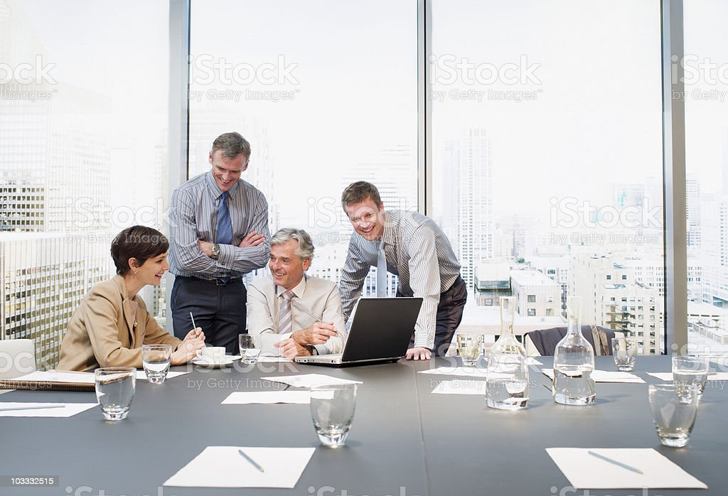 Business people working at laptop in conference room overlooking city royalty-free stock photo