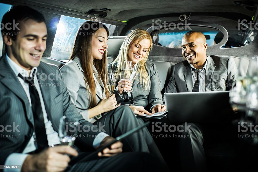 Business people working in a limousine and drinking champagne. royalty-free stock photo