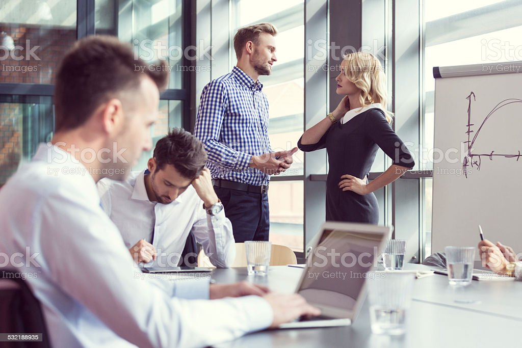 Business people working in an office Four business people working in a board room, discussing, using laptop.  2015 Stock Photo