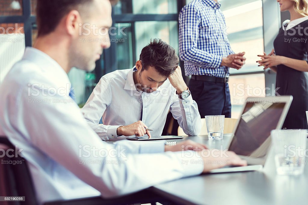 Business people working in an office Four business people working in an office. Businessmen sitting at the table using laptop and digital tablet.  2015 Stock Photo