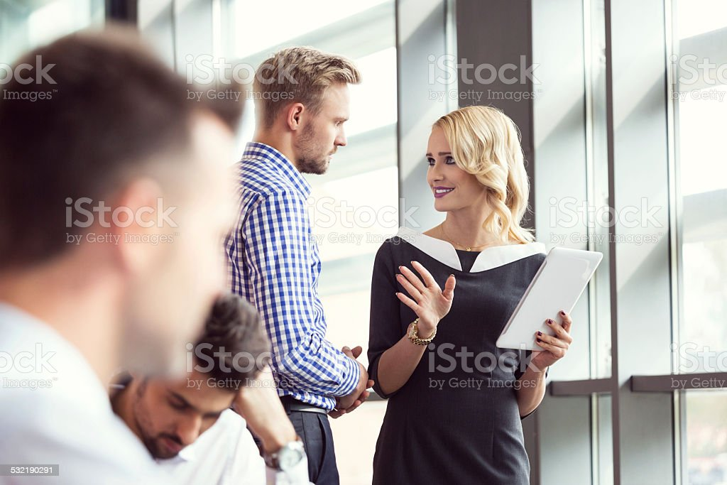 Business people working in an office Four business people working in an office. Focus on two coworkers discussing project on digital tablet.  2015 Stock Photo