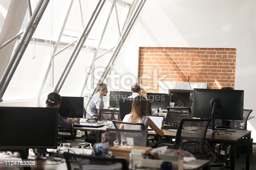 1090214584 istock photo Business people working in coworking open space 1124783328