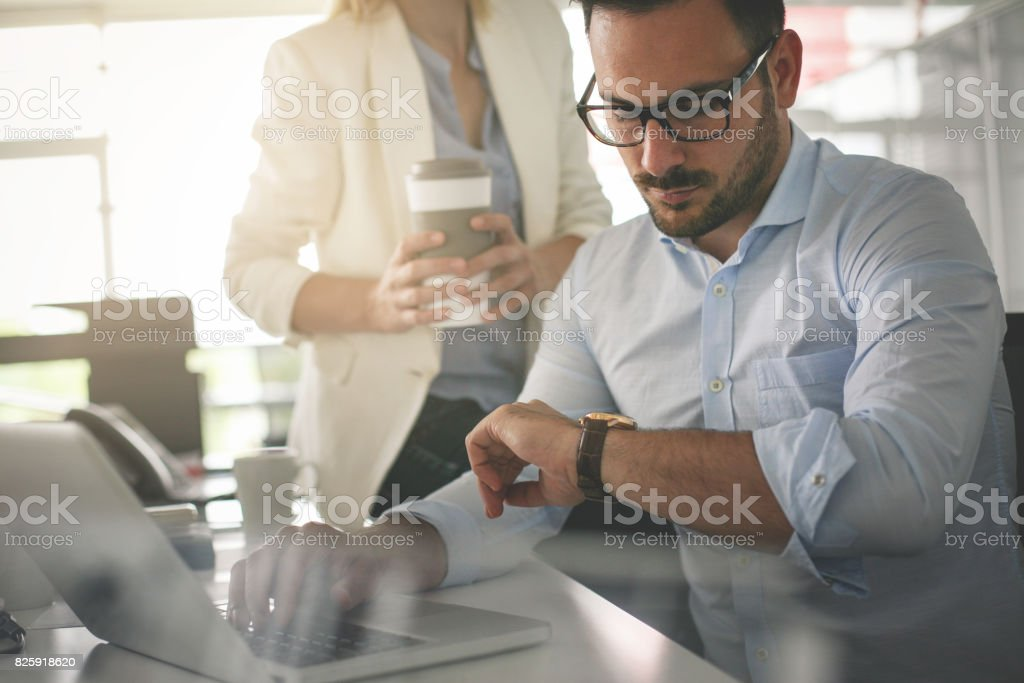 Business people working in office. Business man looking at clock an waiting something. stock photo