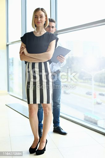 Portrait of gorgeous female and male standing near big window. Corporates posing and looking at camera calmness and happiness. Man and woman discussing project. Office interior