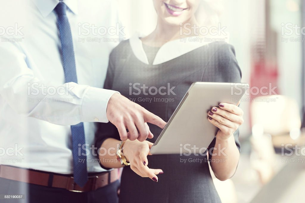 Business people working on digital tablet in an office Businesswoman and businessman using a digital tablet in an office. Close up of hands. 2015 Stock Photo