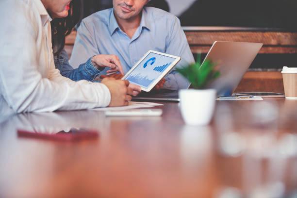 Geschäftsleute auf finanzielle Daten auf einem digitalen Tablet. – Foto
