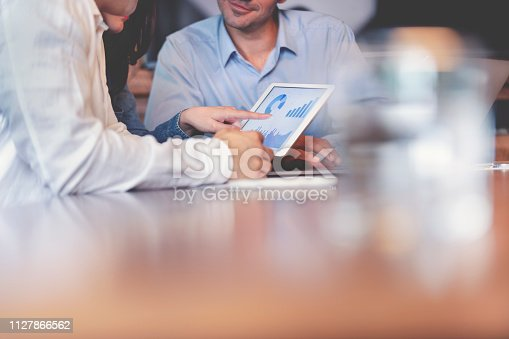 Business people working on financial data on a digital tablet. One looks like the manager working with employees, or a financial advisor. It may also be a training session. All are dressed in business casual clothing.