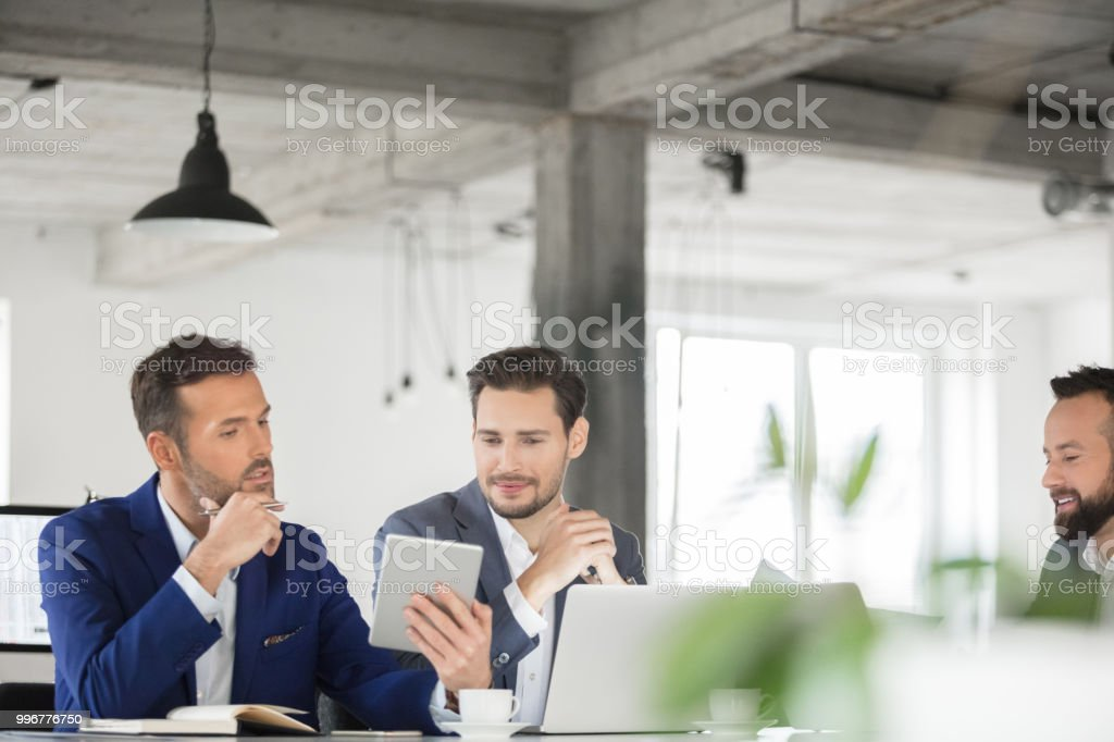 Business people working on new business project Portrait of three business colleagues looking at digital tablet and discussing work. Mature businessman showing digital tablet and sharing his ideas with colleagues. Adult Stock Photo