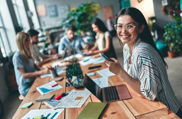Business people working Group of young business people are working together in modern office. Creative people with laptop, tablet, smart phone, notebook. Successful hipster team in coworking. Freelancers. business laptop stock pictures, royalty-free photos & images