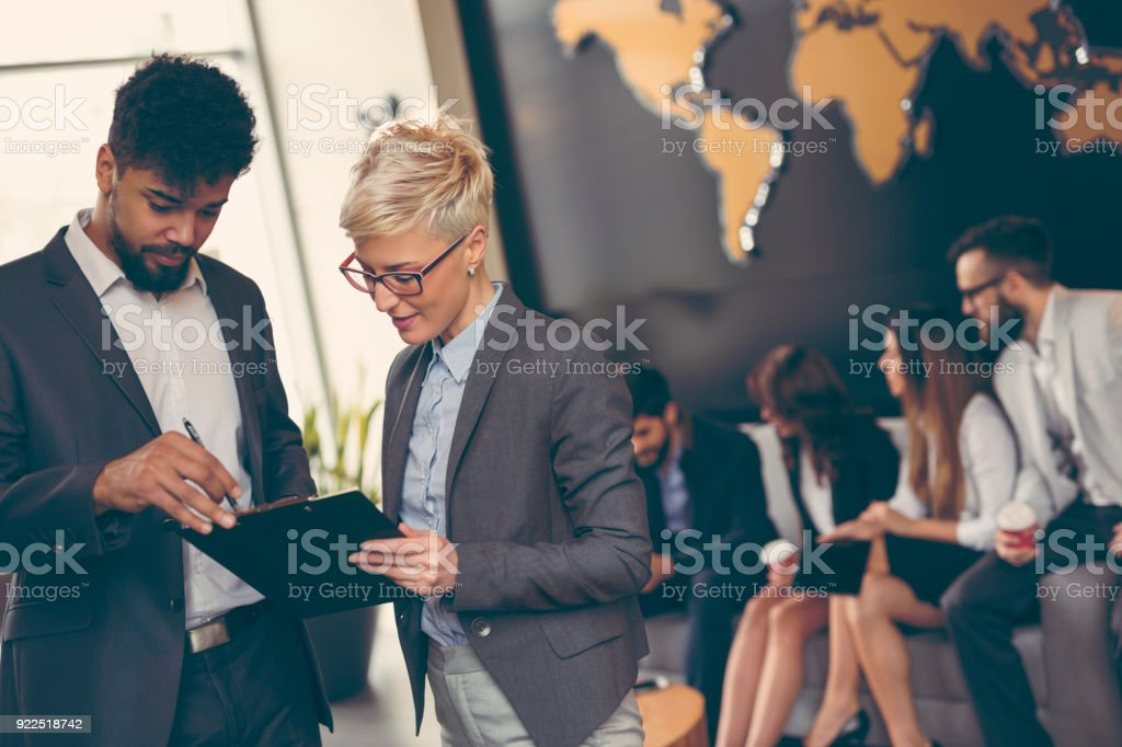 Business people working Businessman and businesswoman reviewing contract; business team working in the background Adult Stock Photo