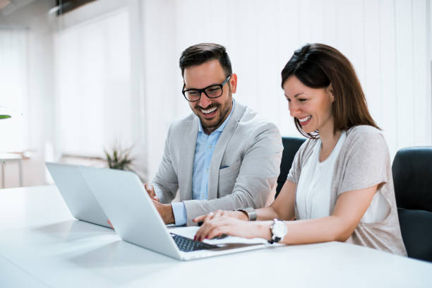 mensen uit het bedrijfsleven werken samen in heldere kantoor, zit op bureau. - man woman stockfoto's en -beelden