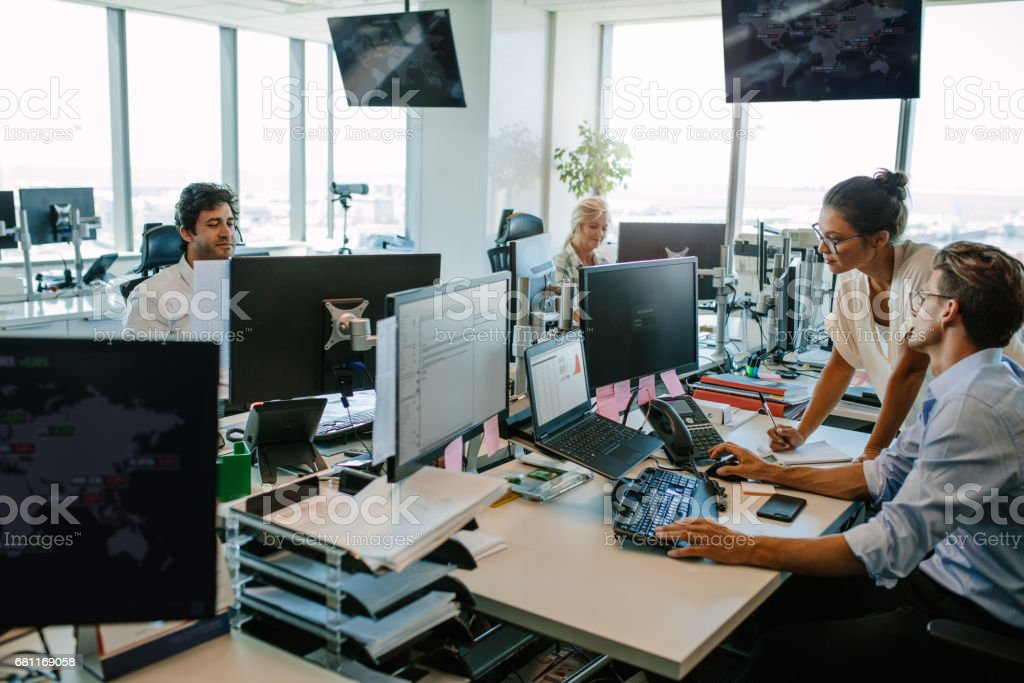 Business people working together in office Business people working in modern office. Team working at desks in busy office. Adult Stock Photo