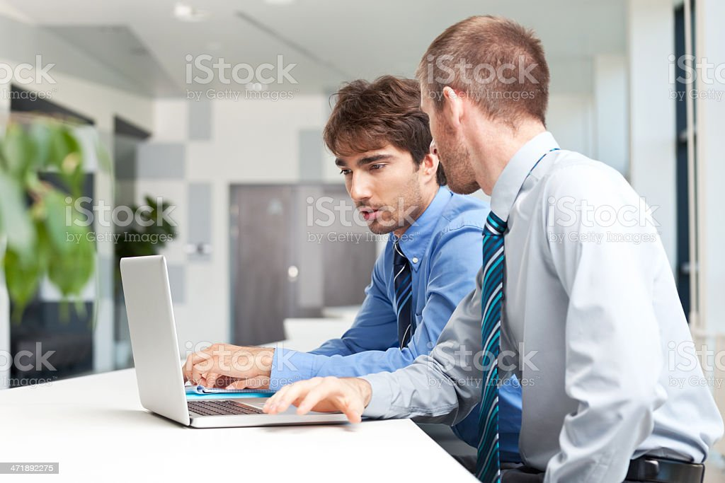 Business people working together Two businessmen sitting in an office and working together on the laptop.  Adult Stock Photo